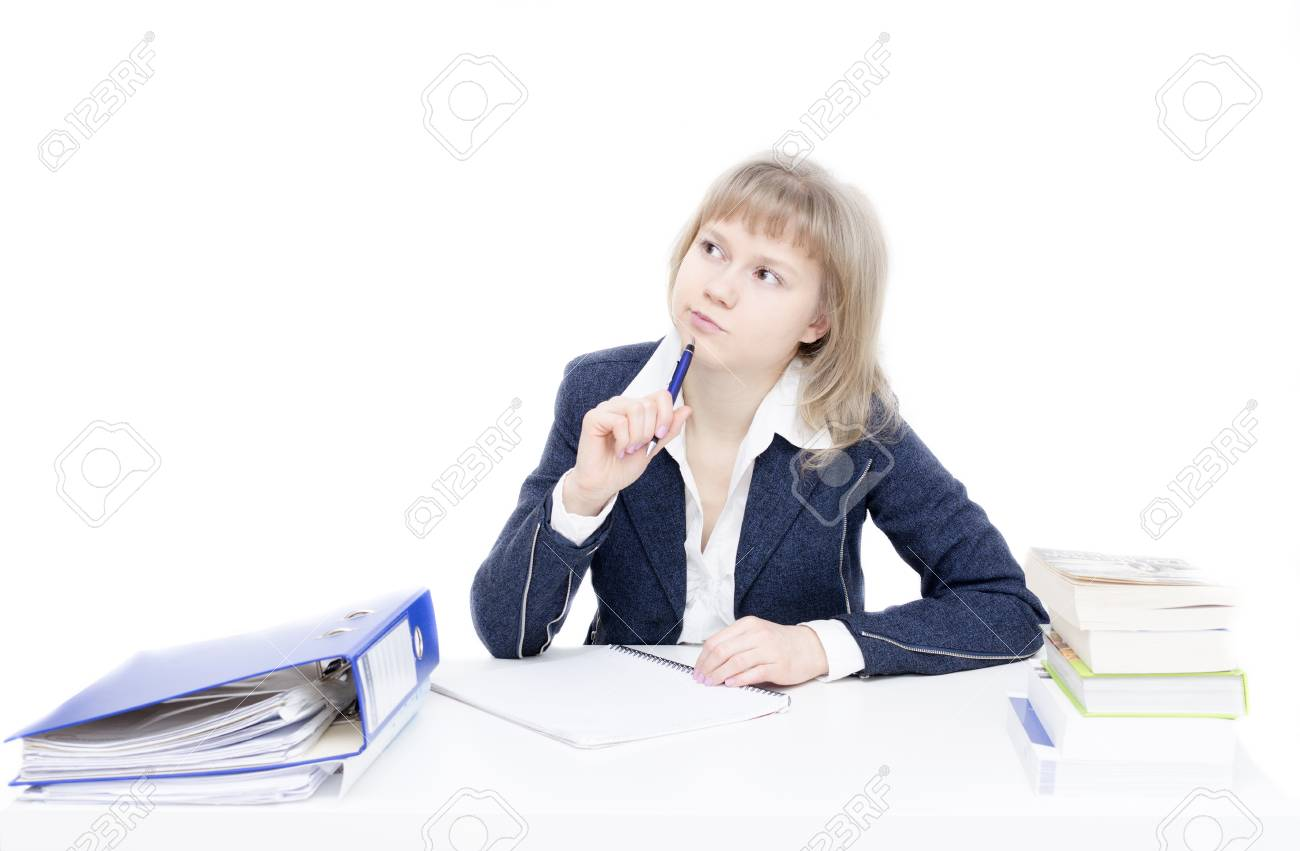 A young woman is sitting at the desk and is studying - 24703240