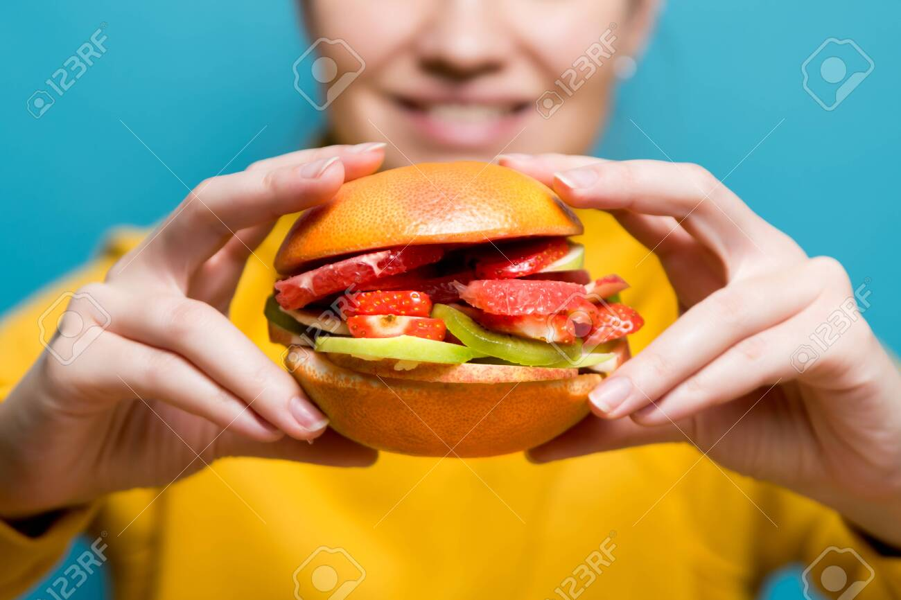 young woman holding a vegetarian burger made of fruits and berries, close up - 149146295
