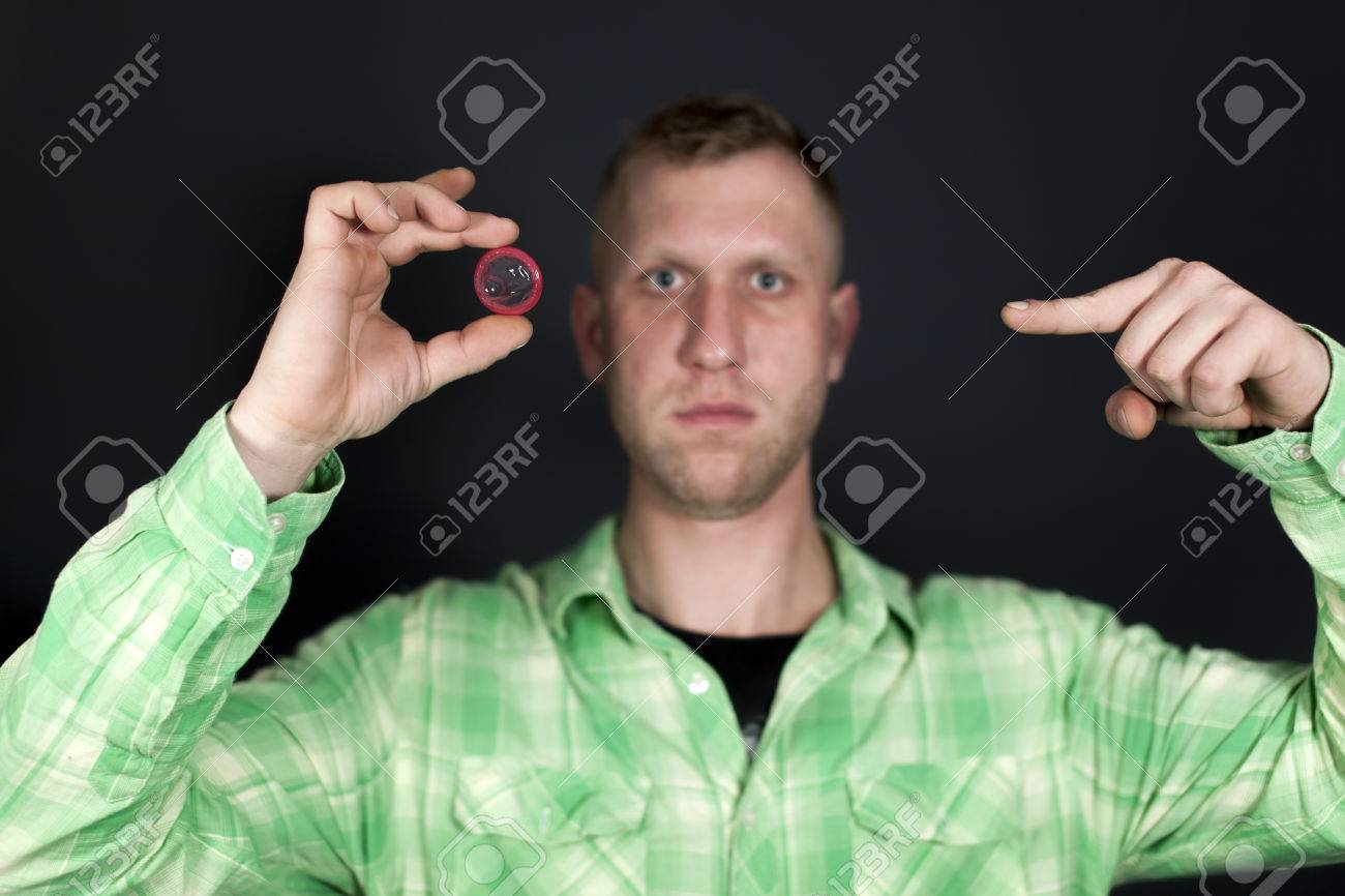 Man show for finger on red condom in front of dark background. Sign OK - 75243653