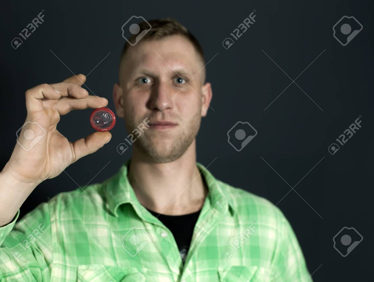 Man show red condom and smile in front of dark background. - 75243659