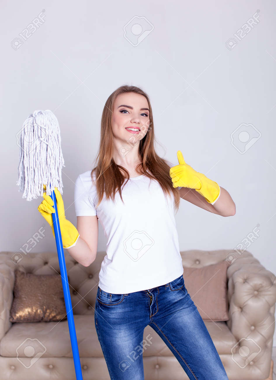 Portrait of happy young woman doing chores cleaning home with floor mop - 74940932