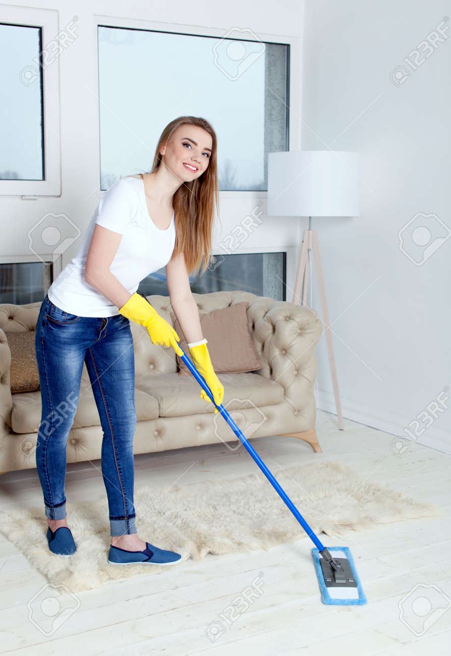 Happy smiling woman housewife with mop cleans floor - 75270587