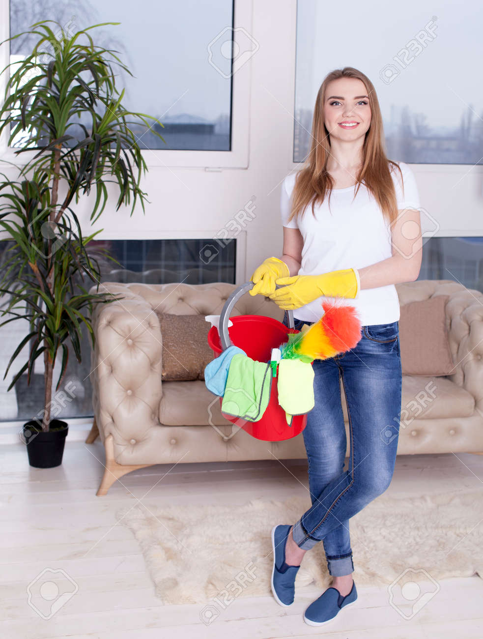 Smiling woman housewife with bucket and cleaning things - 75270585