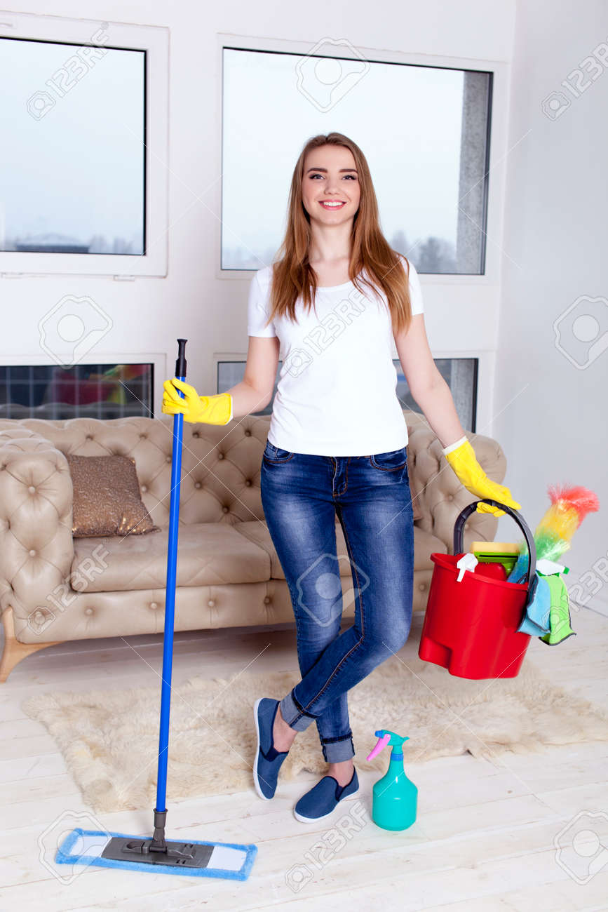Young woman housewife with bucket in hands and cleaning things - 75270591