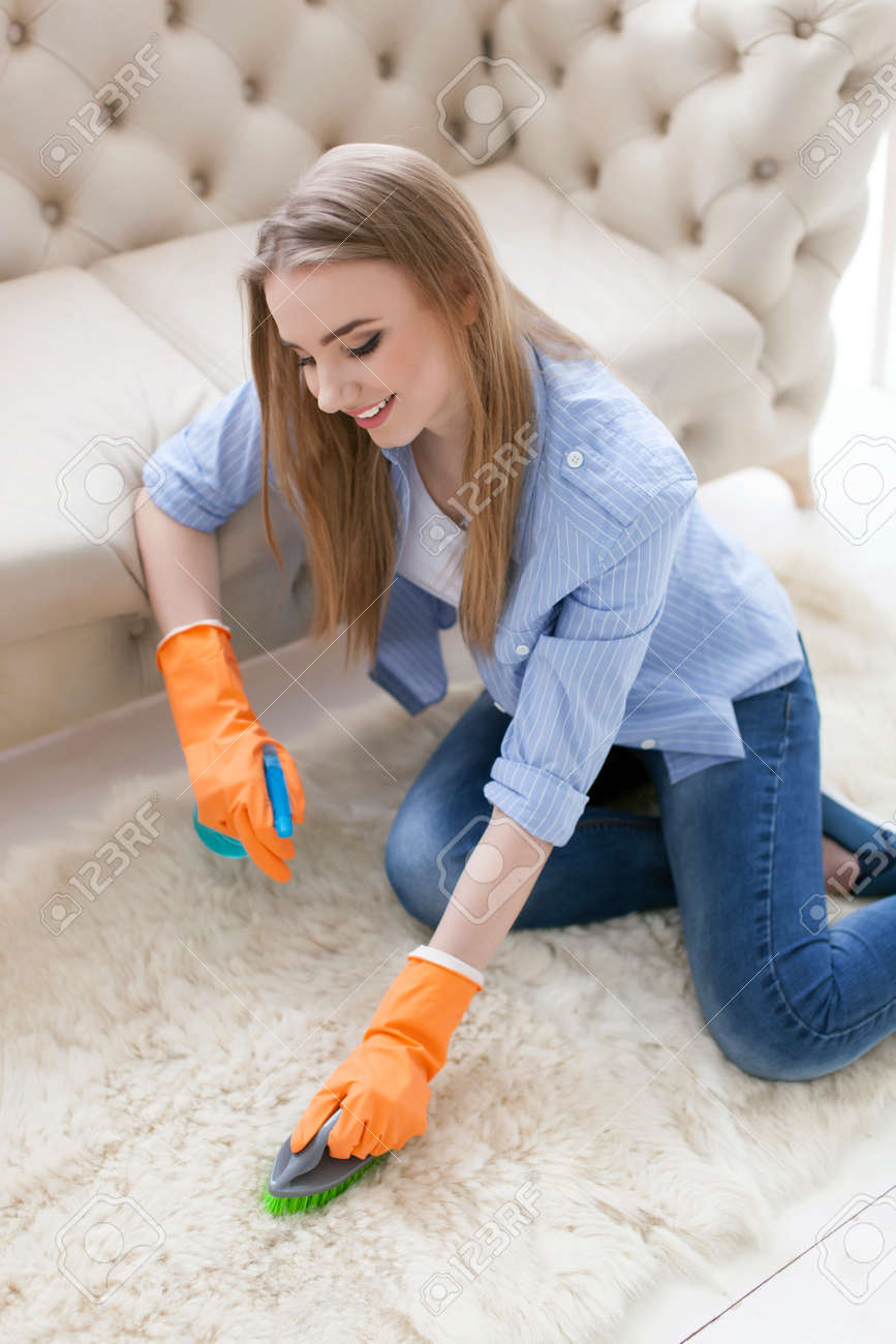 Attractive woman housewife cleans carpet with brush - 75270608