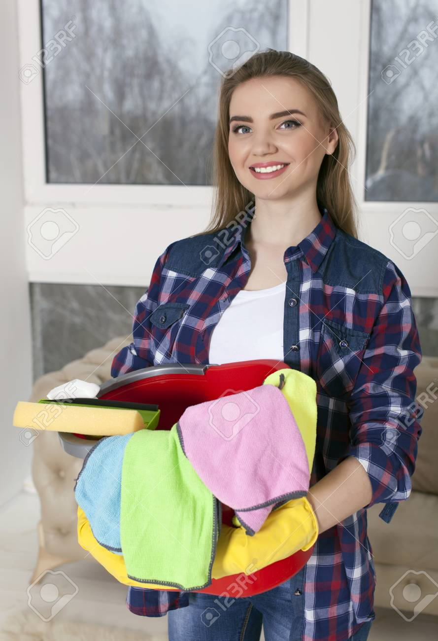Young smiling woman housewife with bucket, towels. Portrait - 75270612