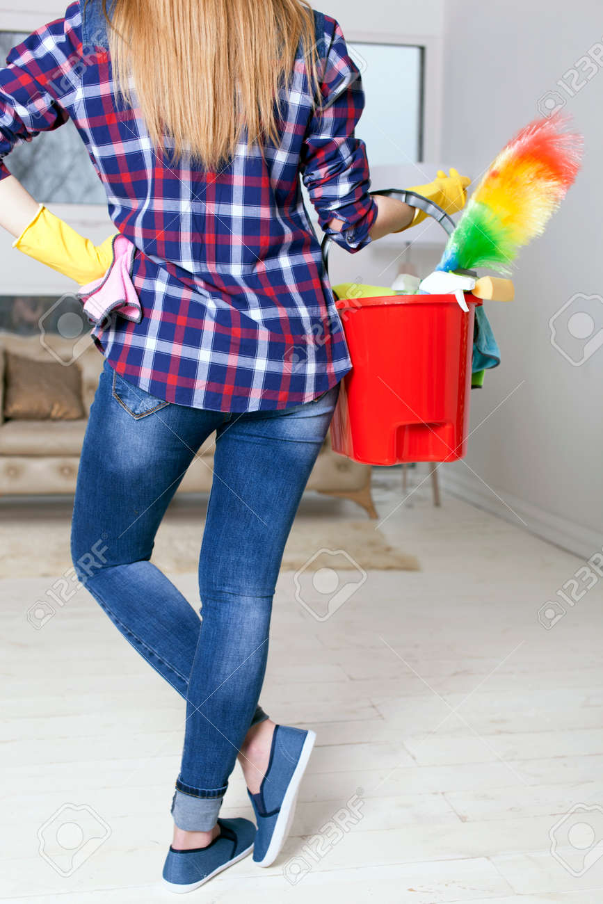 Woman housewife with bucket and towels in hands. Back view - 75270614