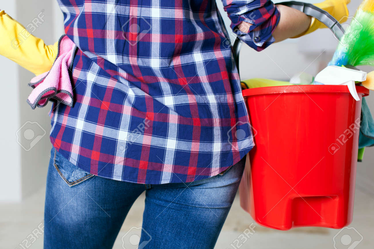 Woman housewife with bucket and towels in hands. Back view close up - 75270615