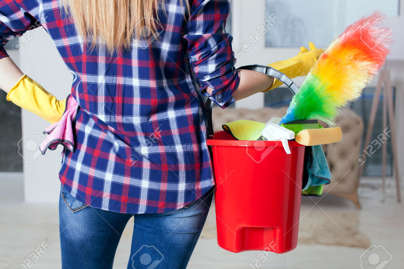 Woman housewife with bucket and towels in hands. Back view close up - 75270617