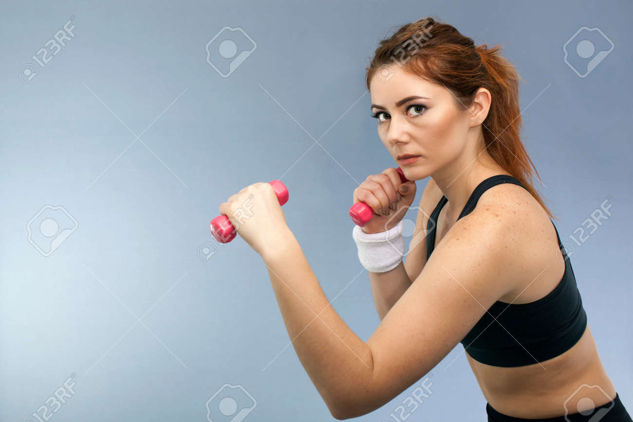 Sport serios girl with red dumbbells looks direct. Portrait - 75276914