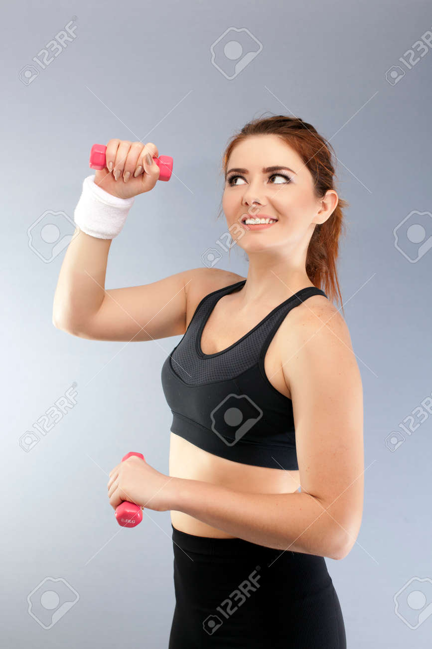 Sport fitness girl with red dumbbells in front of gray background looks up - 75276916