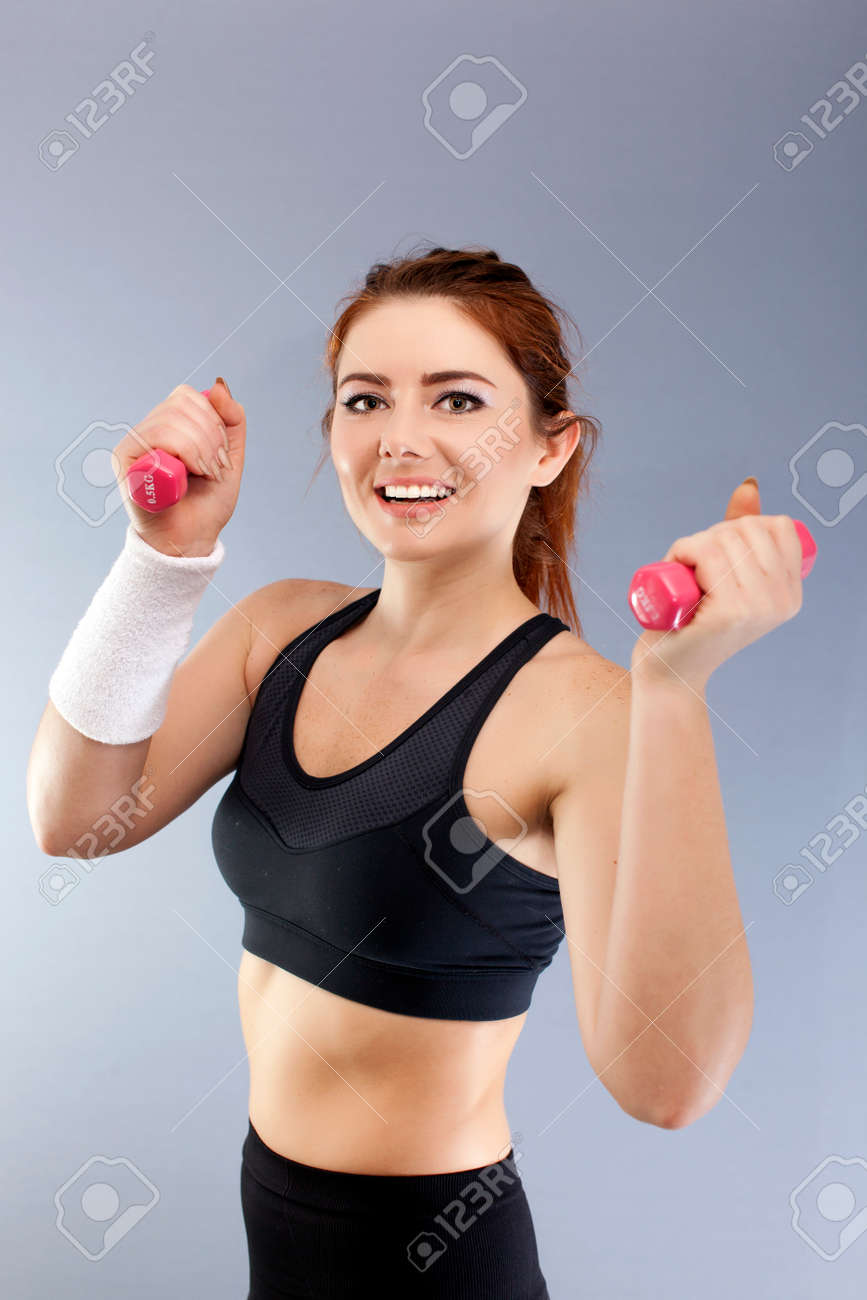 Sport smiling with red dumbbells in front of gray background looks direct - 75276918