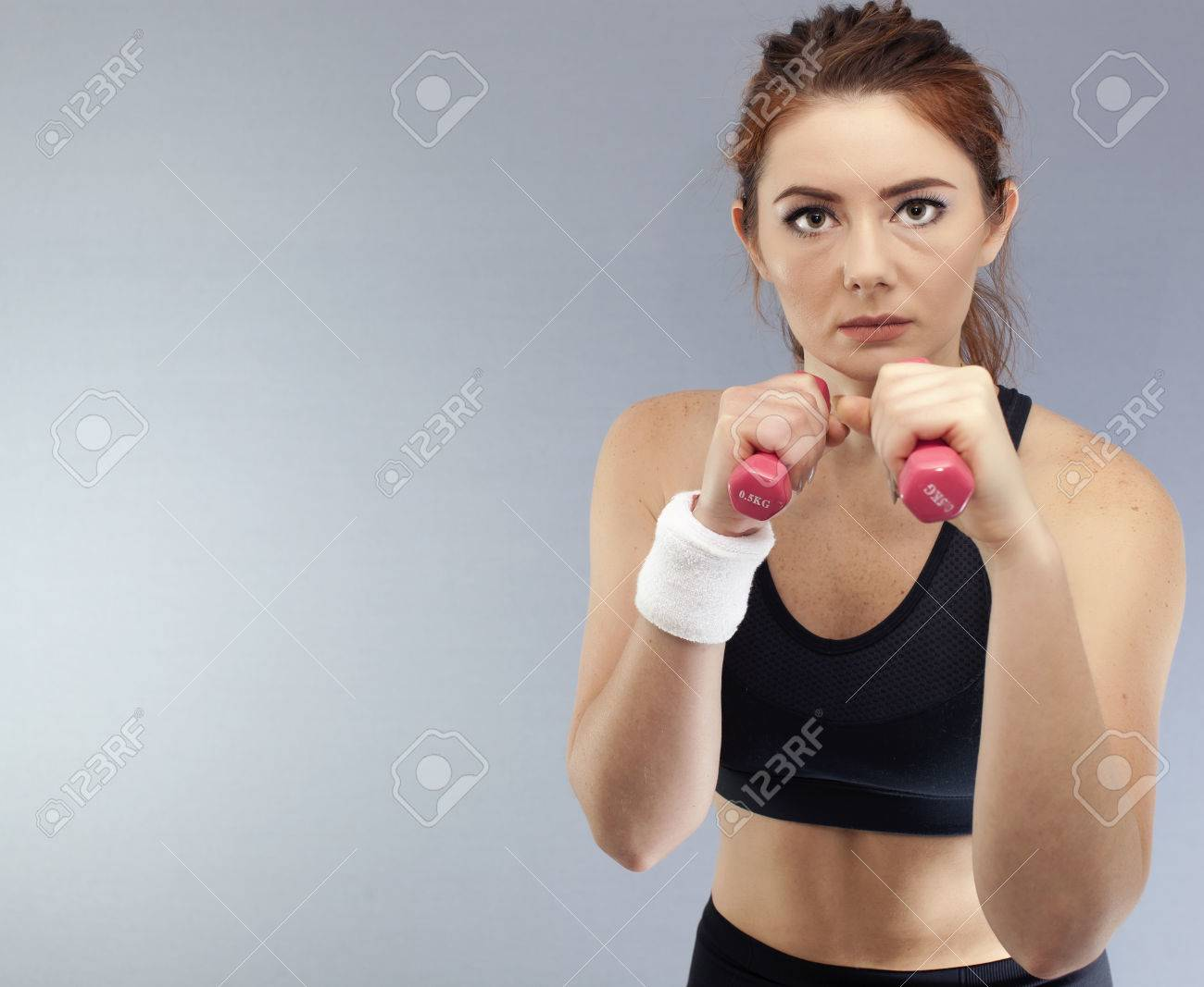 Sport serios girl with red dumbbells boxer pose looks direct. Portrait - 75276921