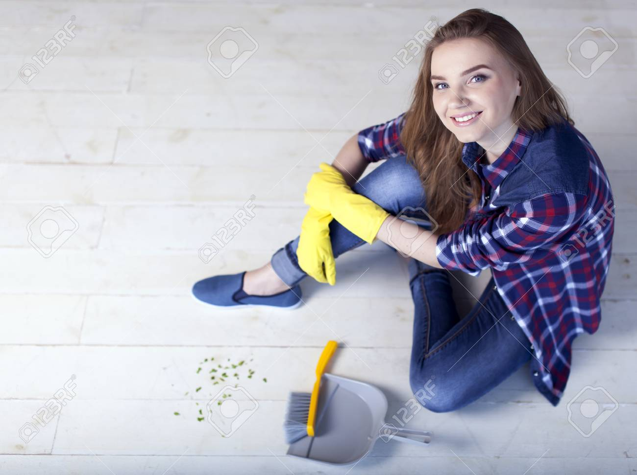 woman sit on floor with scoop for garbage and smile. - 77732566