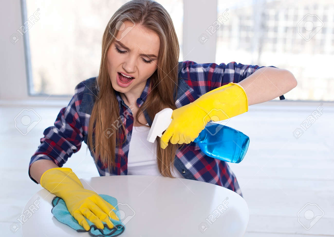 Young woman cleaning dusts on table, emotion on face - 77732561