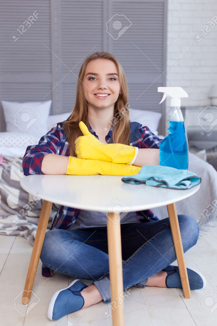 Young woman in yellow gloves of housewife behind little table - 77656430
