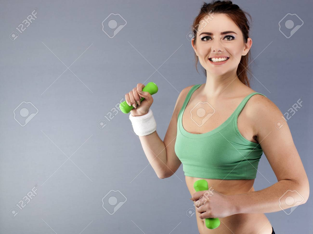 Green dumbbells in hands of fitness young woman. Sport team - 78009957