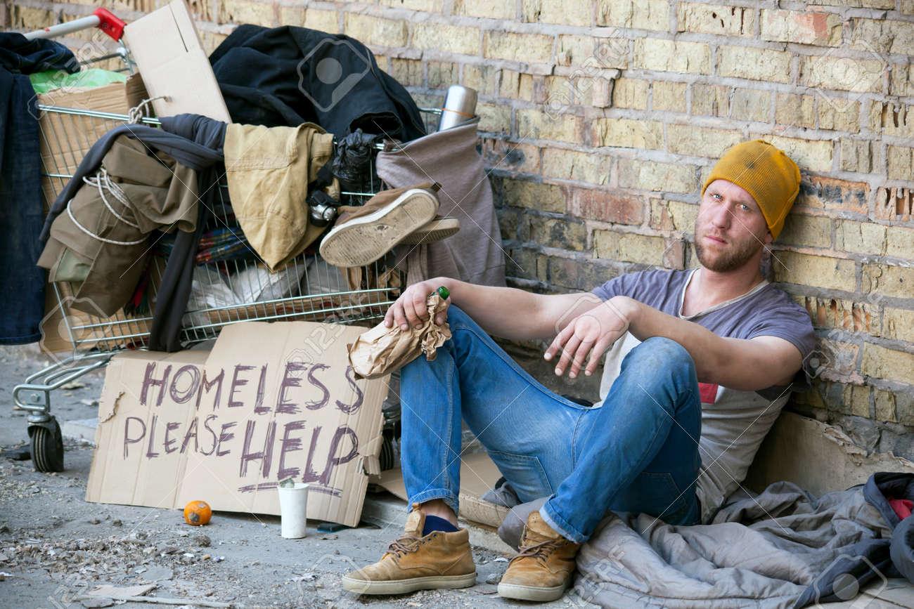 Sad homeless man with cardboard, sits near wall. Carriage is home - 78022977