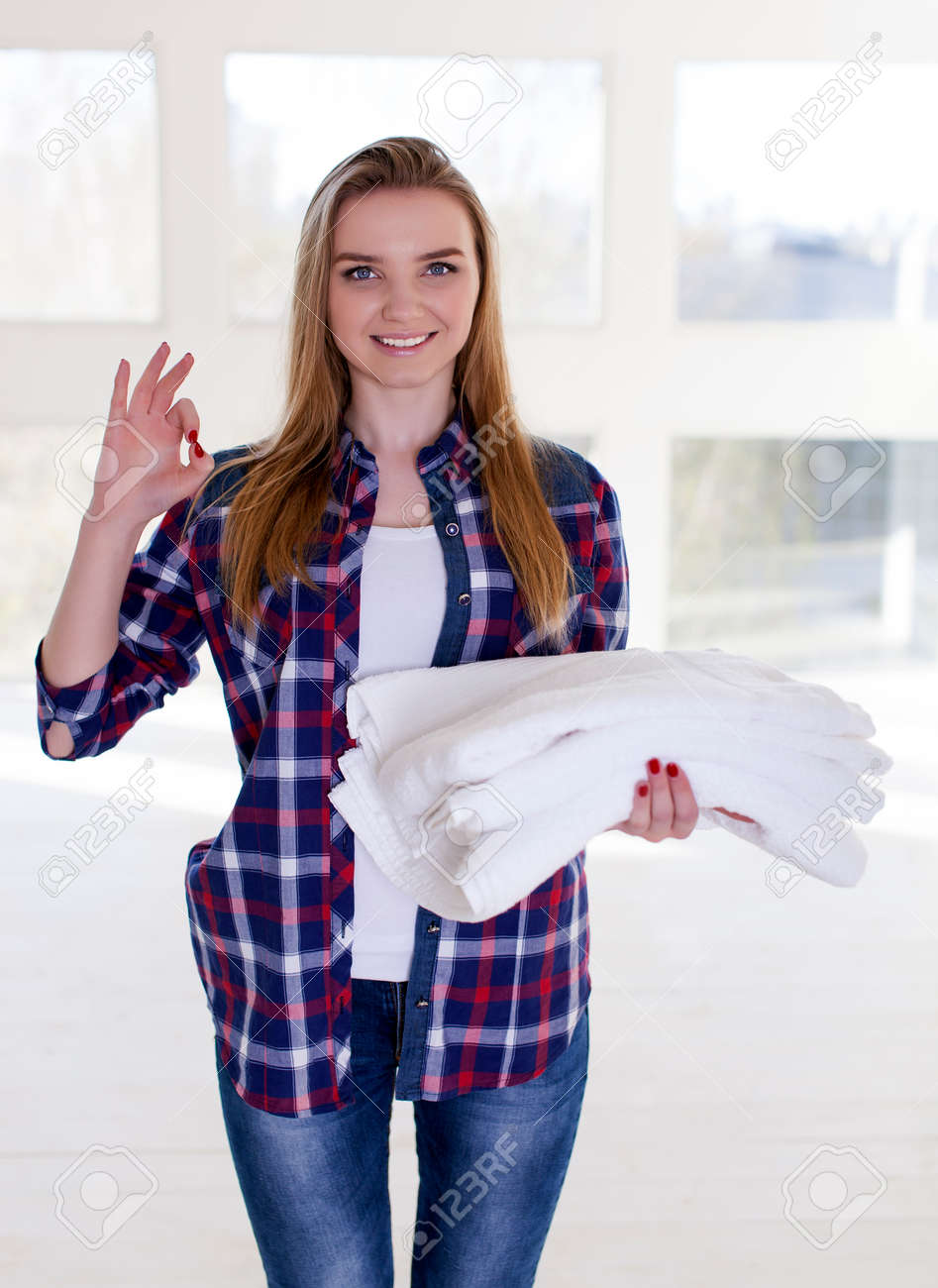 Happy young woman with towels in hands. - 77974965