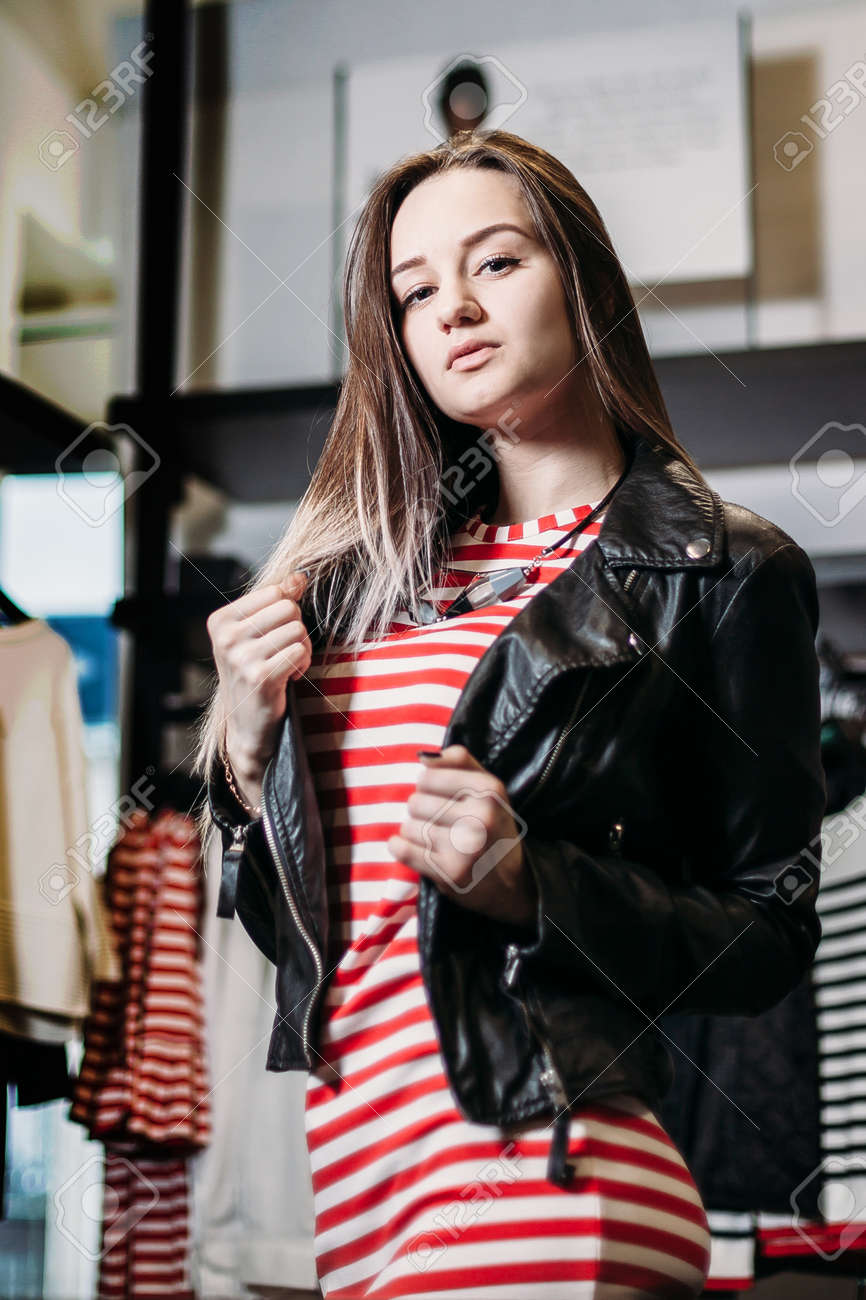 3e30d1a84db2 Stock Photo - The young pretty woman choosing, trying and buys dresses at shop  clothing. Banner for online store clothing. Girl posing in fashionable ...