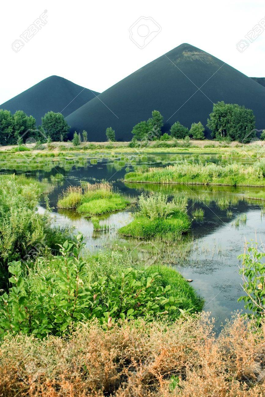marsh and the black mountains of slags in Kazakhstan, Asia Stock Photo - 4326347