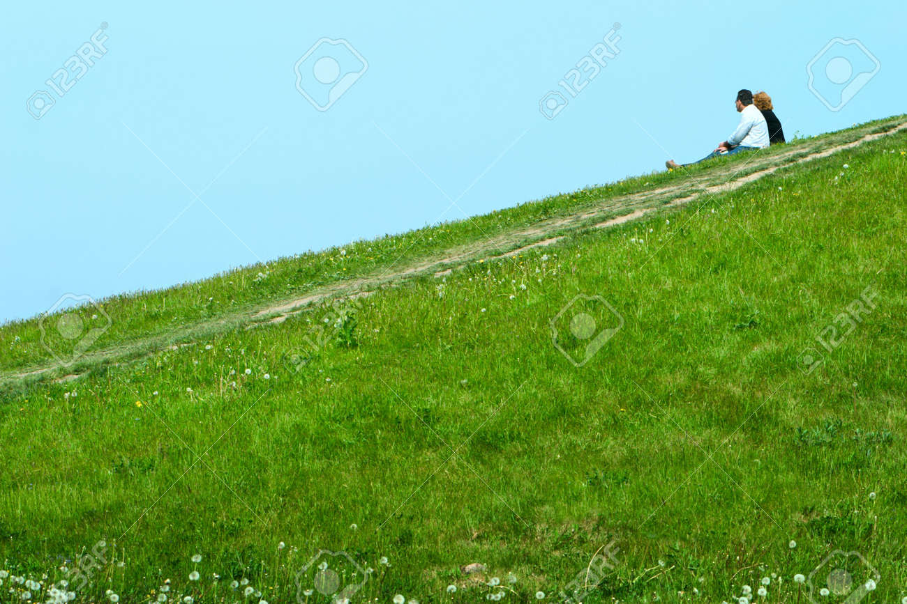 family couple seating on green slope and dreaming something about Stock Photo - 4692698