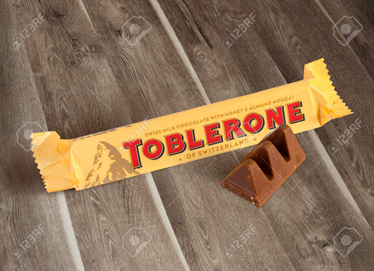 Chisinau, Moldova - June 14, 2016: A bar of Toblerone - Swiss milk chocolate with honey and almond nougat on a wood background. With clipping path. - 62366458