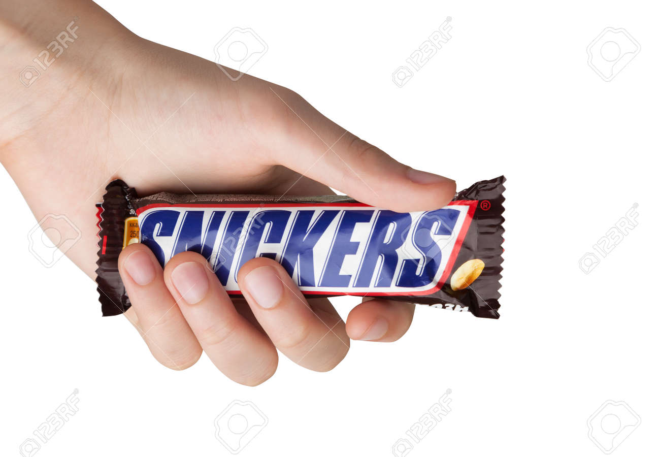 Hand holding a Snickers chocolate bar - 92221818