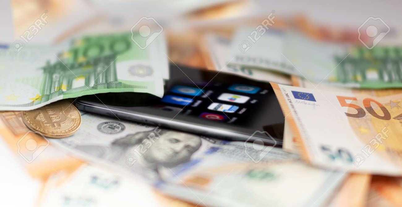 Mobile banking and finance concept: smartphone with applications, euro, US dollar banknotes, and bitcoin. Business background. Blurred concept - 170242733