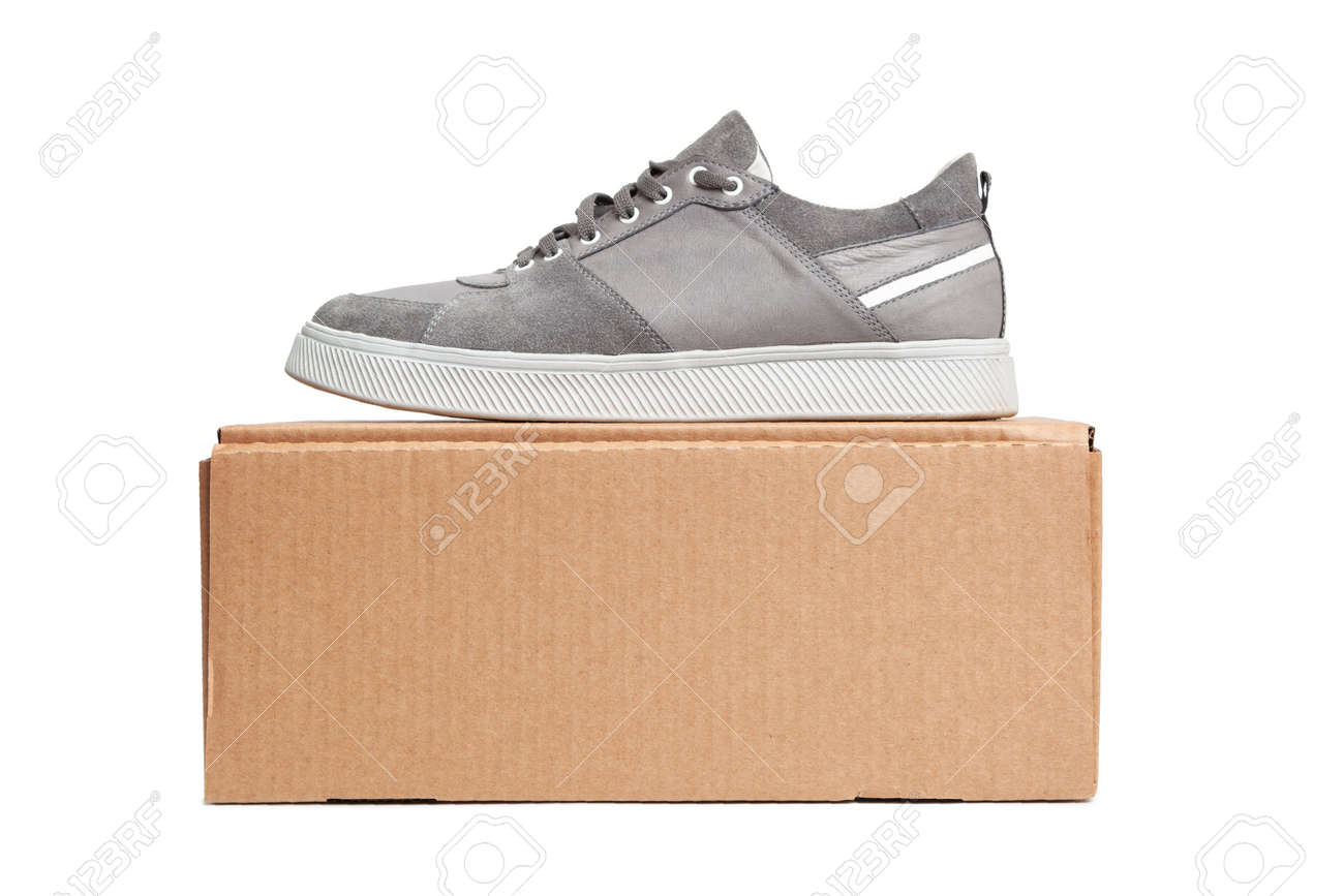 Gray casual sports shoes, sneaker on a brown cardboard box isolated on a white background - 170242763