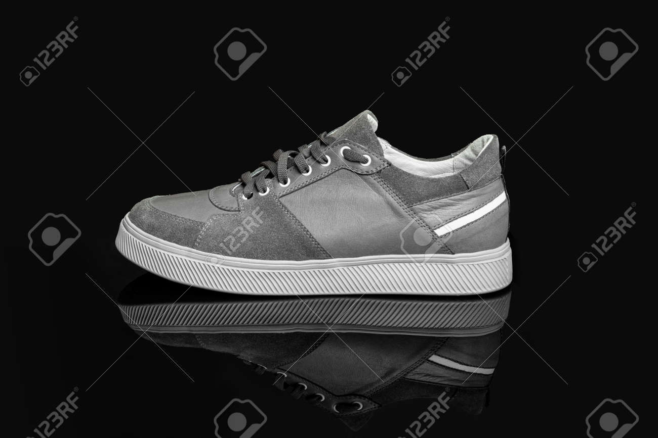 Gray casual sports shoes, sneaker isolated on a black background - 170242765