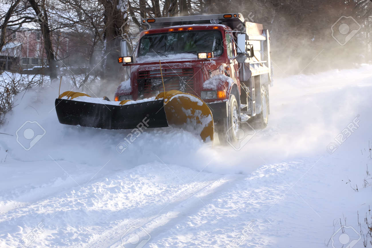 A snowplow truck removing snow from a tree lined rural road on a cold winter day. - 32520660