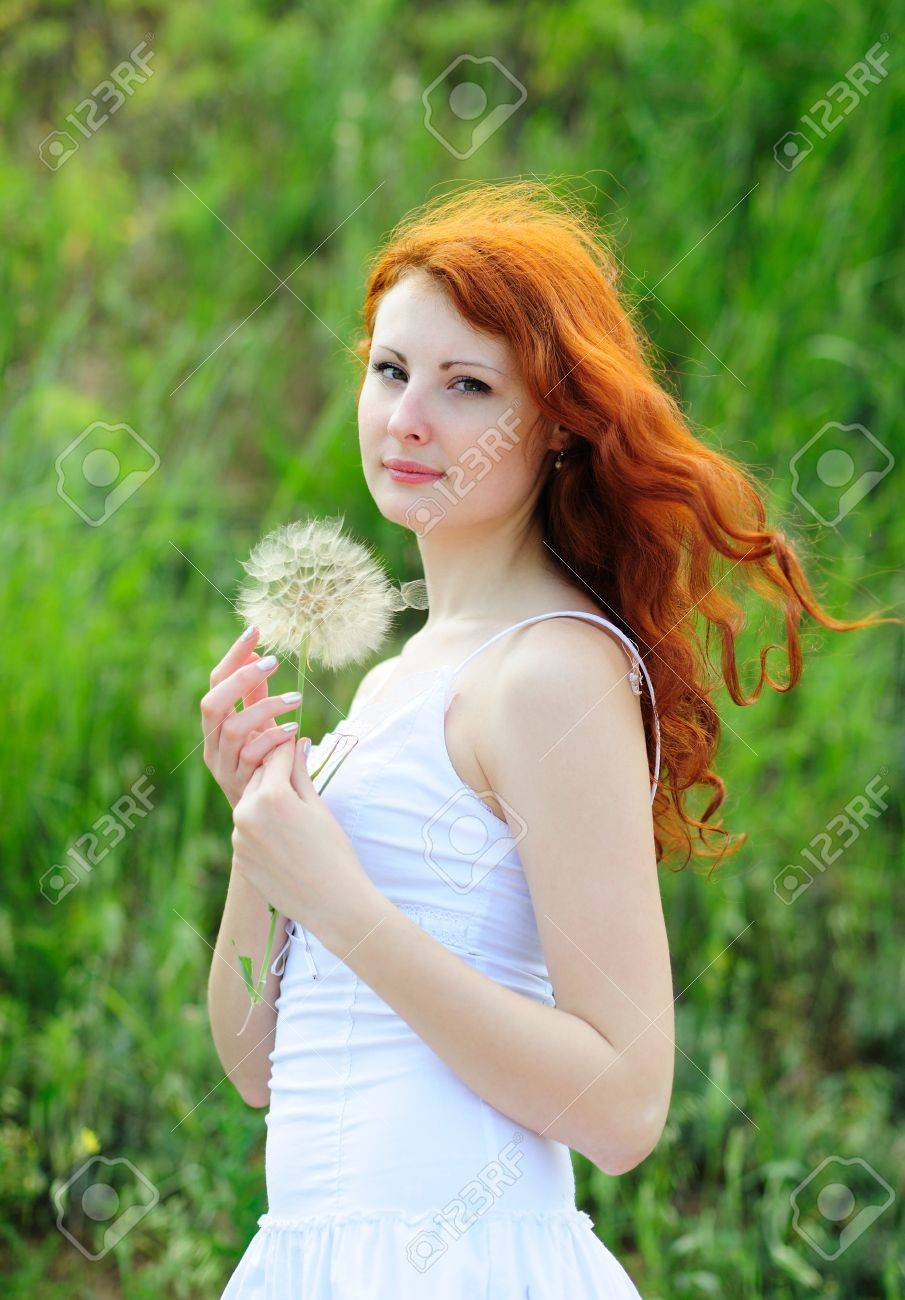 Cute young redhead female with big dandelion in her hands - 7316155
