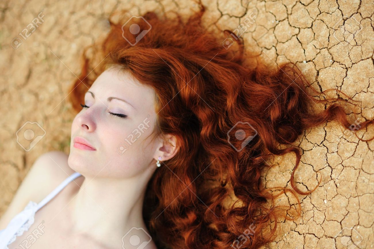 Beauutiful young woman with red hair on the dried up ground - 7364600