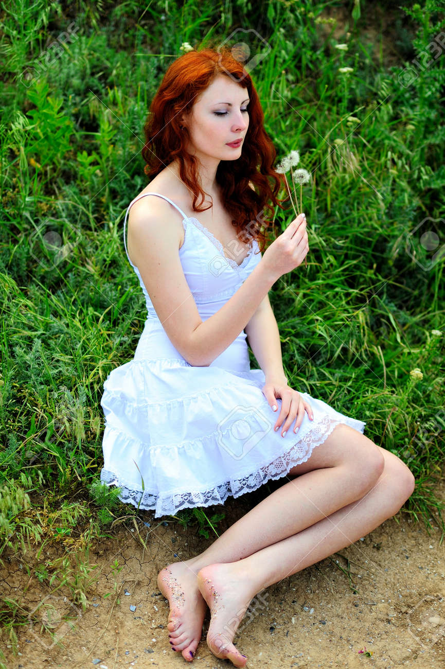 Cute redhead girl who was blowing on a dandelions in her hands. Stock Photo - 9529876