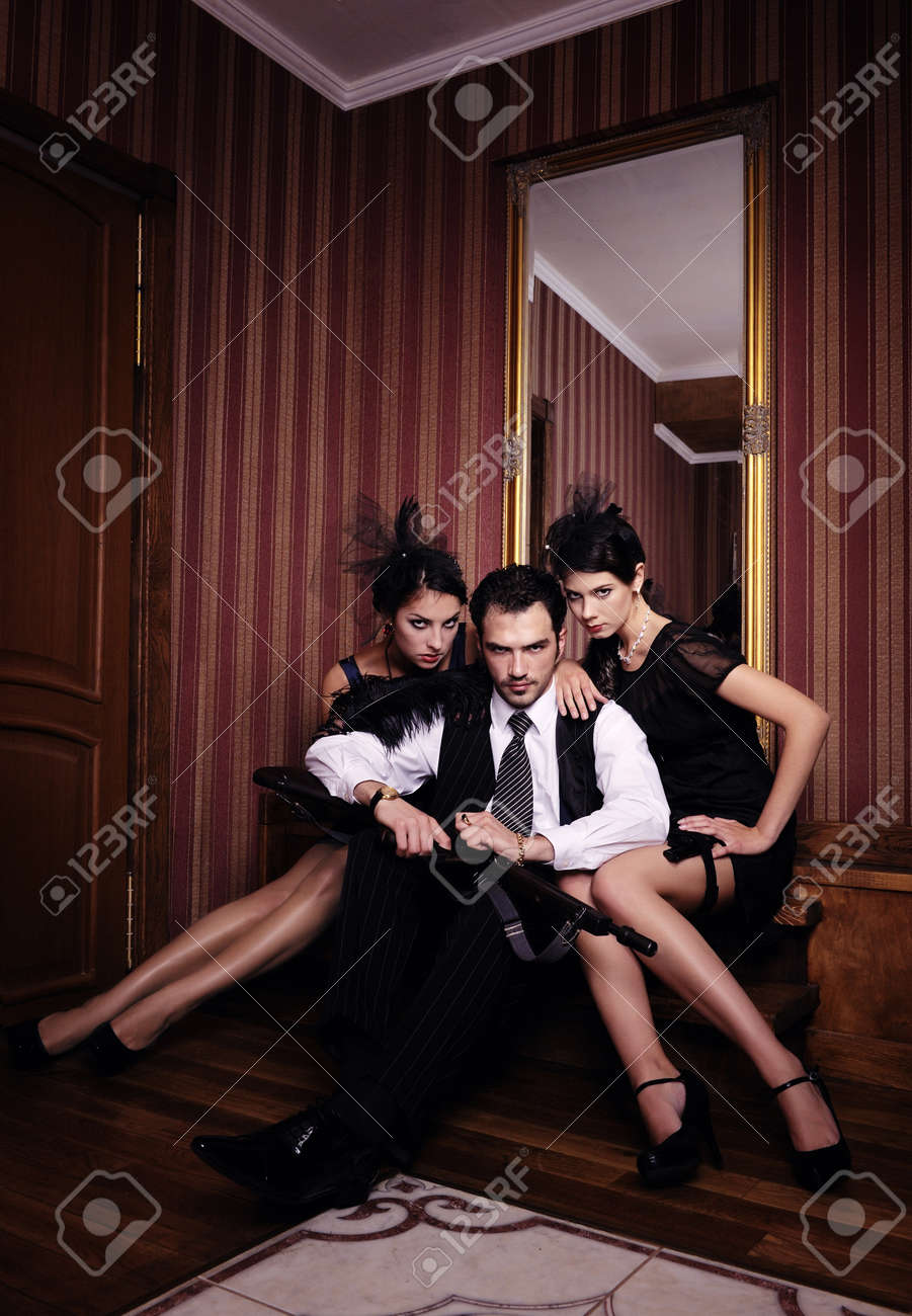 A guy and two beautiful young women in the image of gangsters with guns, looking in camera. Stock Photo - 9999667