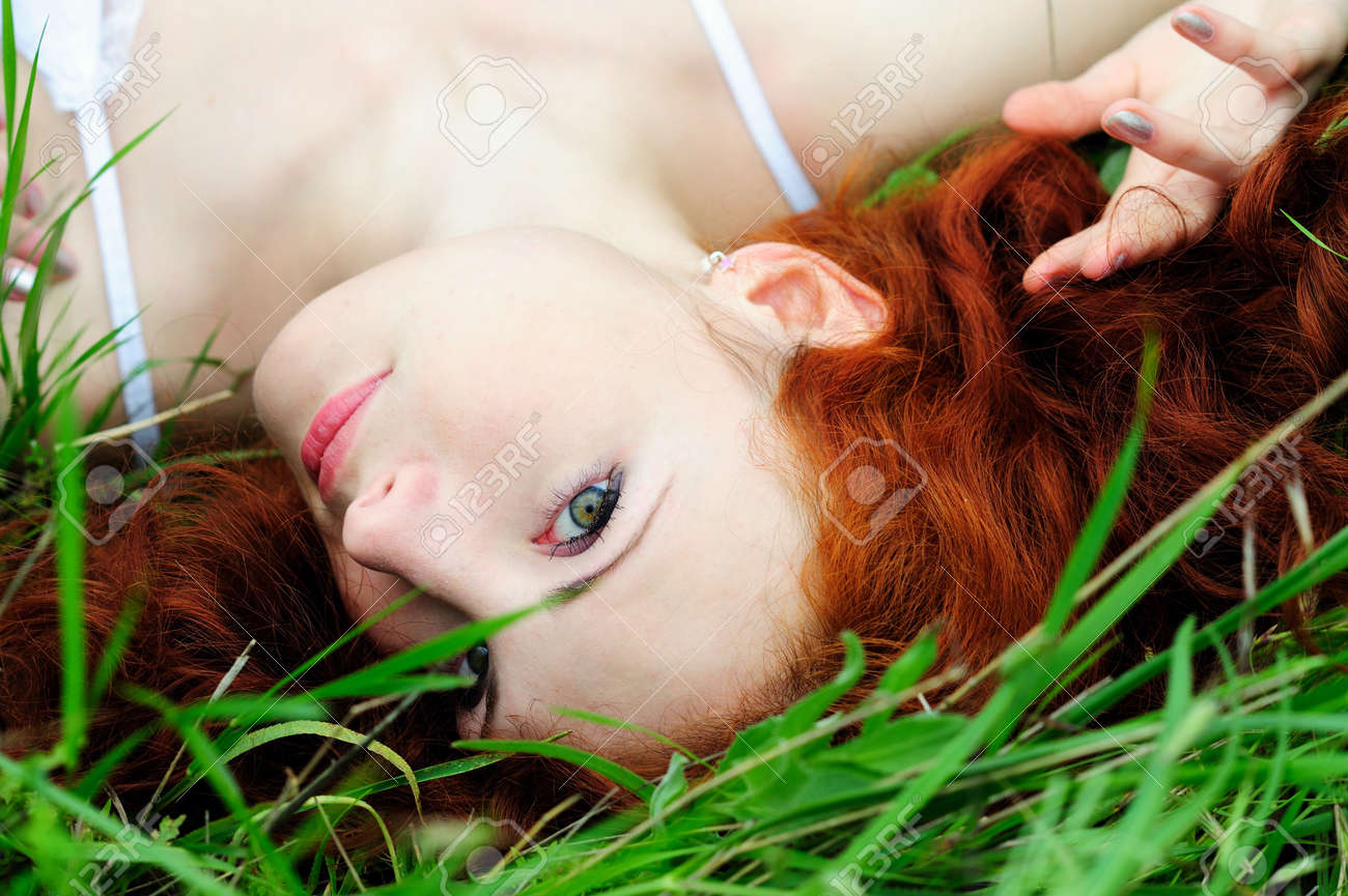 Smiling happy girl portrait, lying in grass field  Outdoor Stock Photo - 13184299