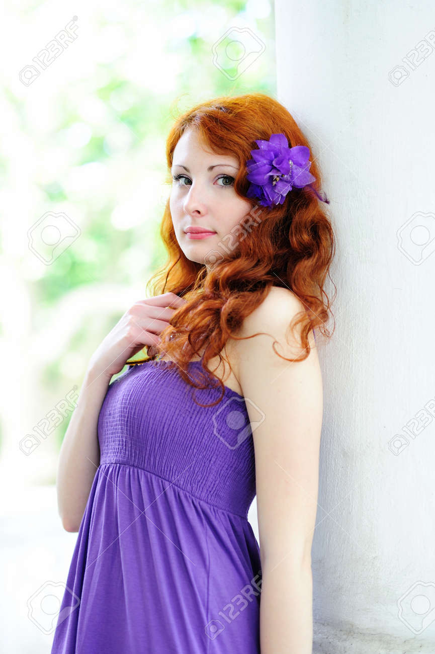 Young beautiful redhead woman portrait with flower in her hair. Outdoor. Stock Photo - 13403444