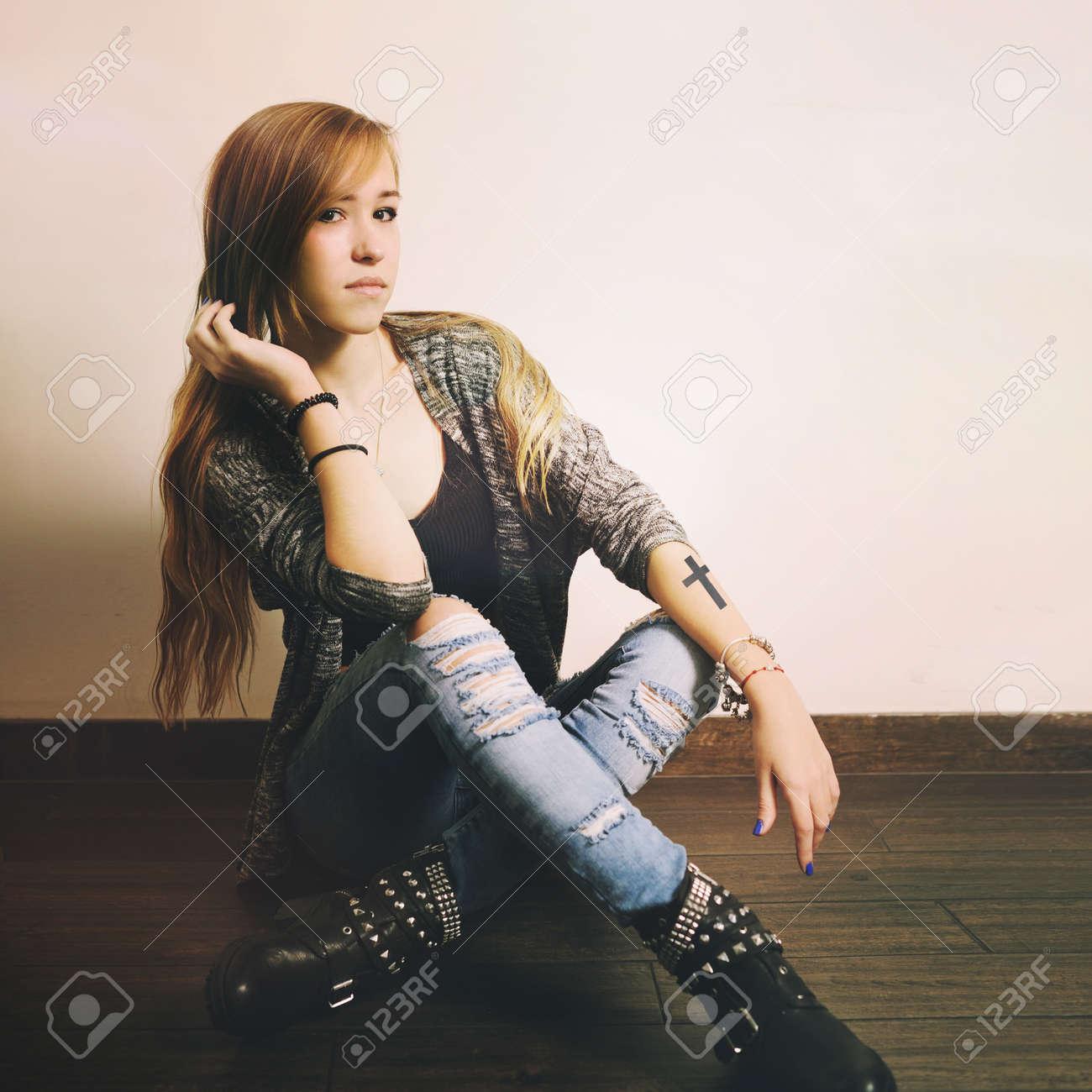 Jeune Femme Caucasien Avec Le Tatouage Croix Sur Une Main Assis Sur
