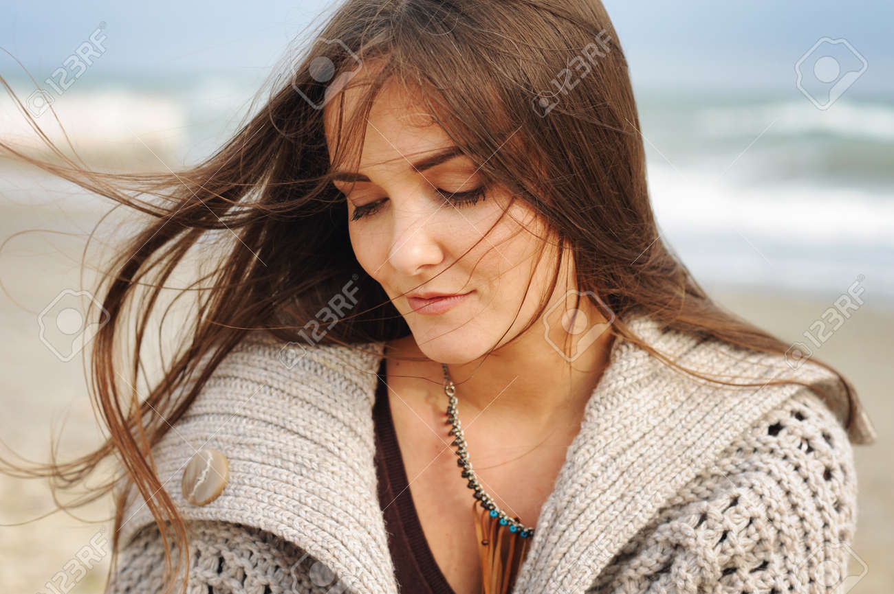 Beautiful young happy woman portrait against seascape, long hair fluttering in the wind, looking down, casual autumn fashion, healthy lifestyle - 67680810