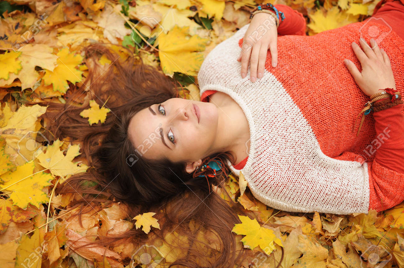 Smiling happy womanl portrait, lying in autumn leaves, dressed in fashion sweater, autumn outdoor - 129016331
