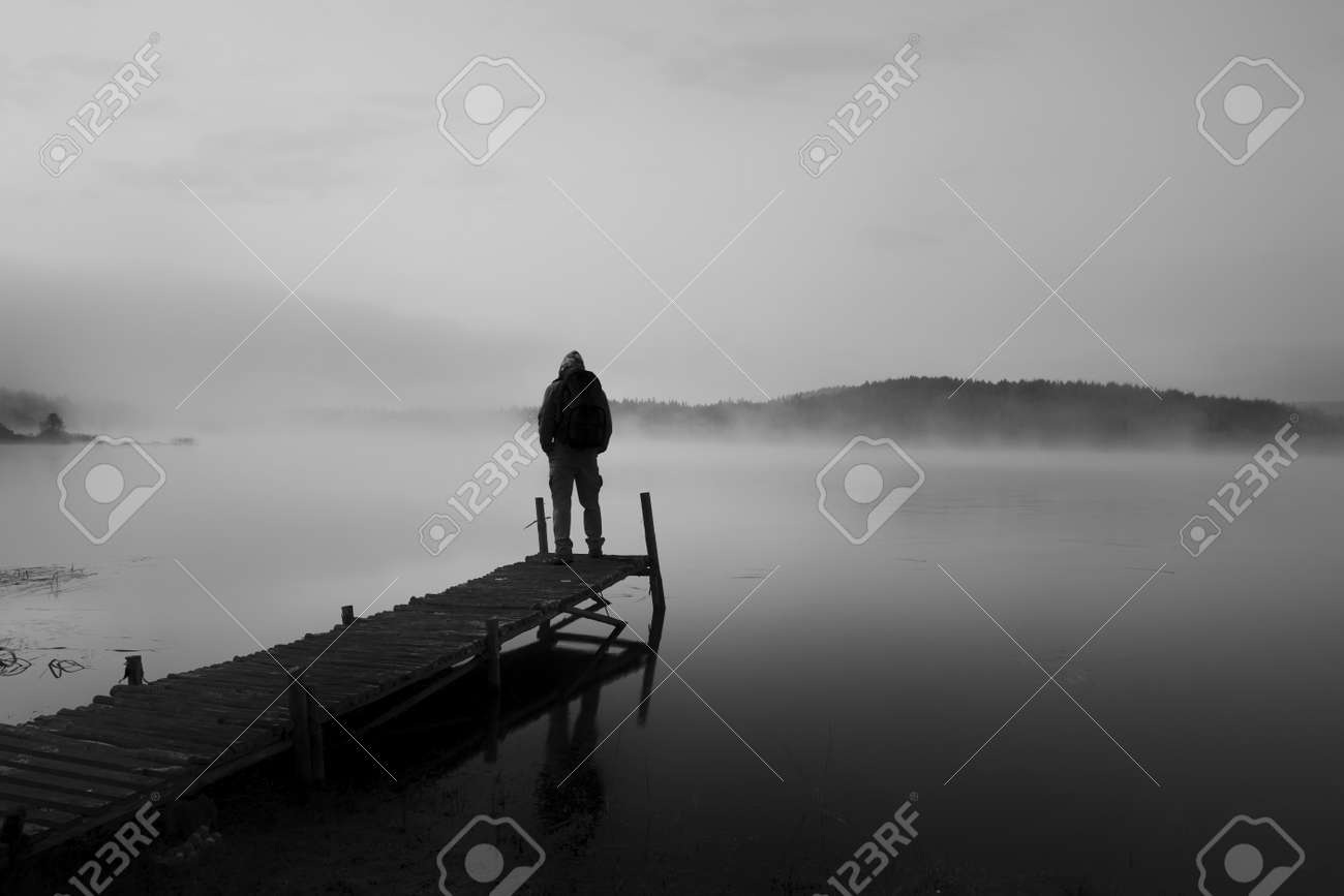 black and white abstract landscape with man stand on wooden bridge in sunrise lake stock photo