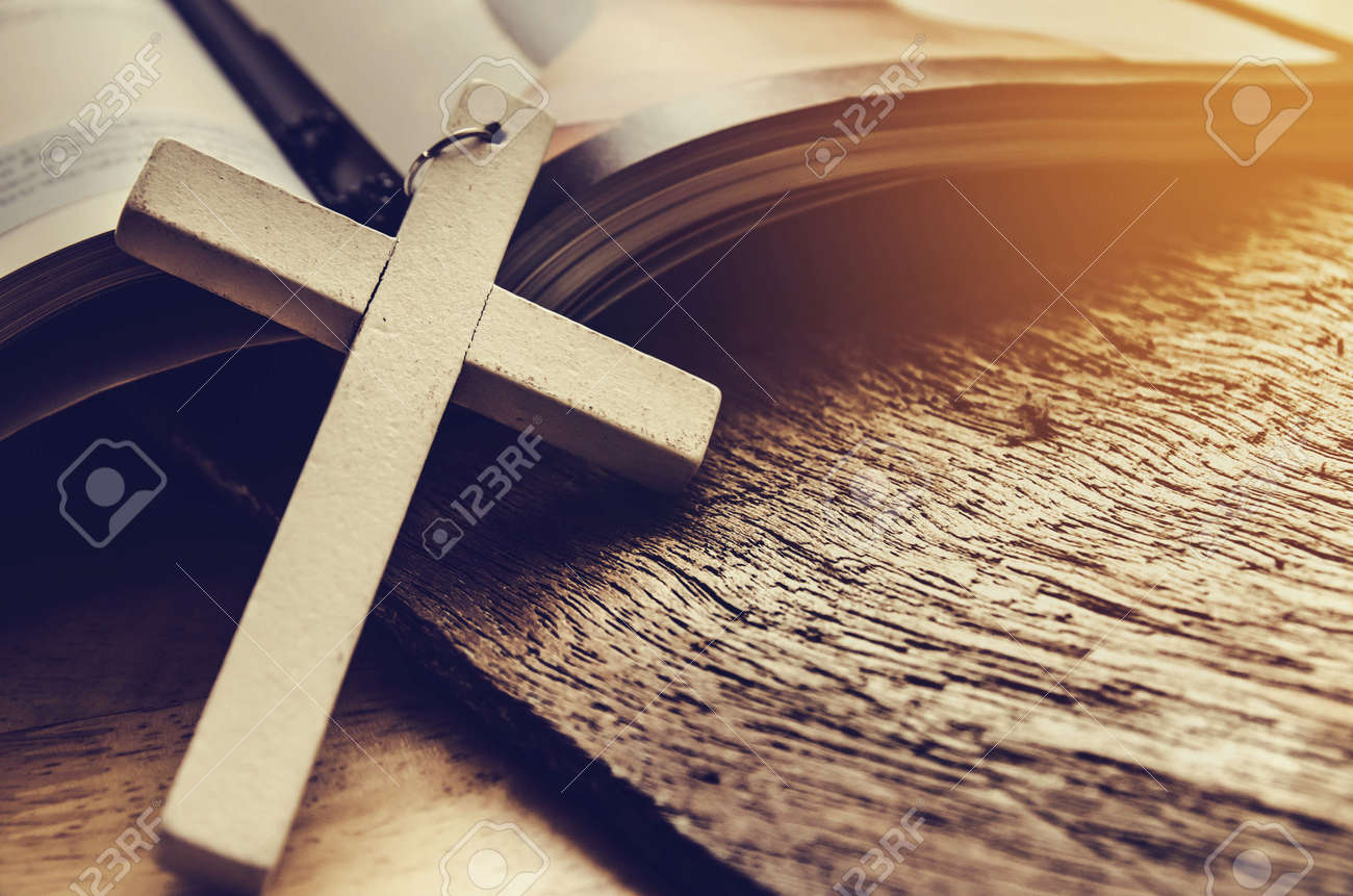 Closeup of simple wooden Christian cross necklace on Bible , vintage tone , god - 58229537
