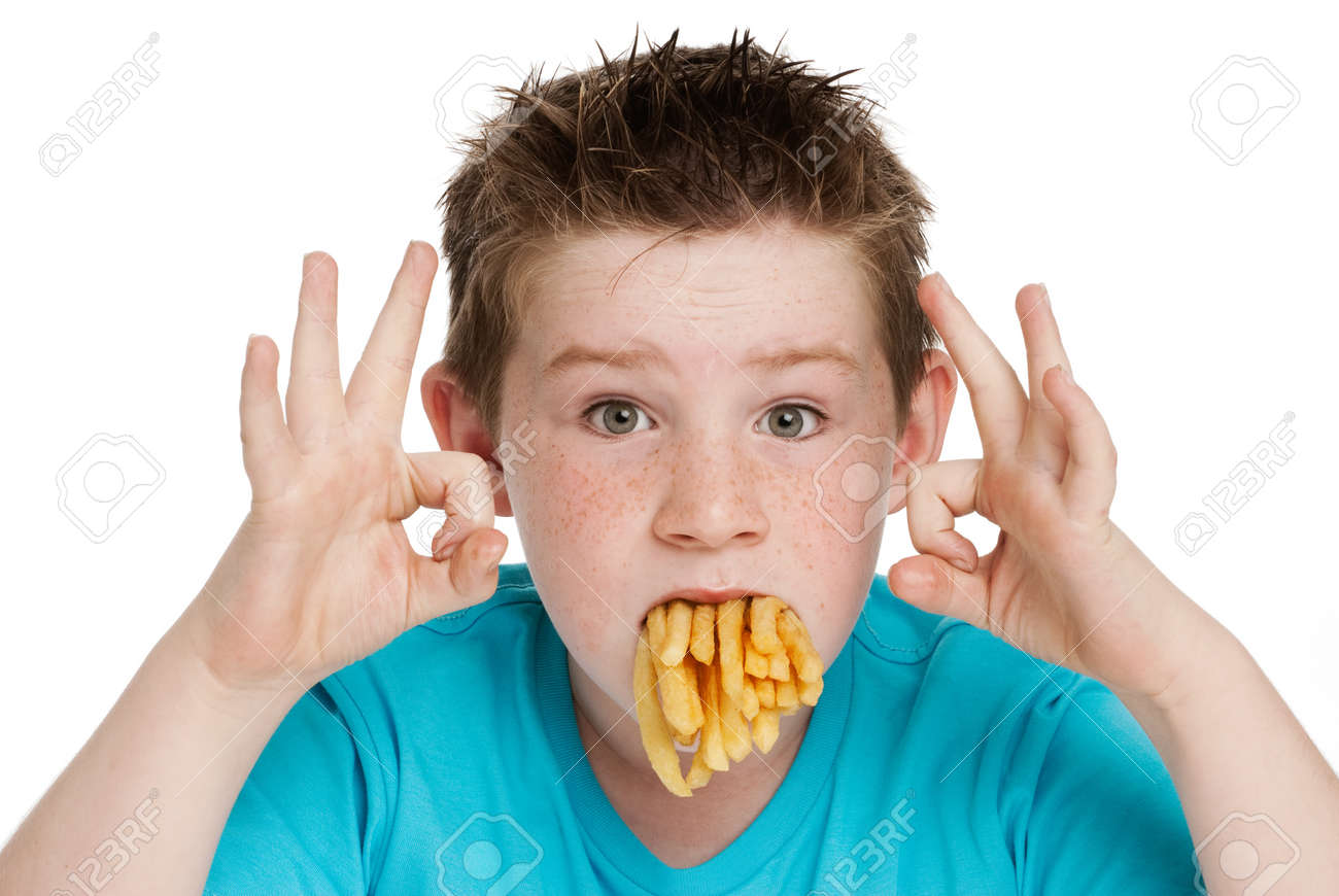 Young boy with a mouth full of chips fries. Isolated on white background. - 20726336