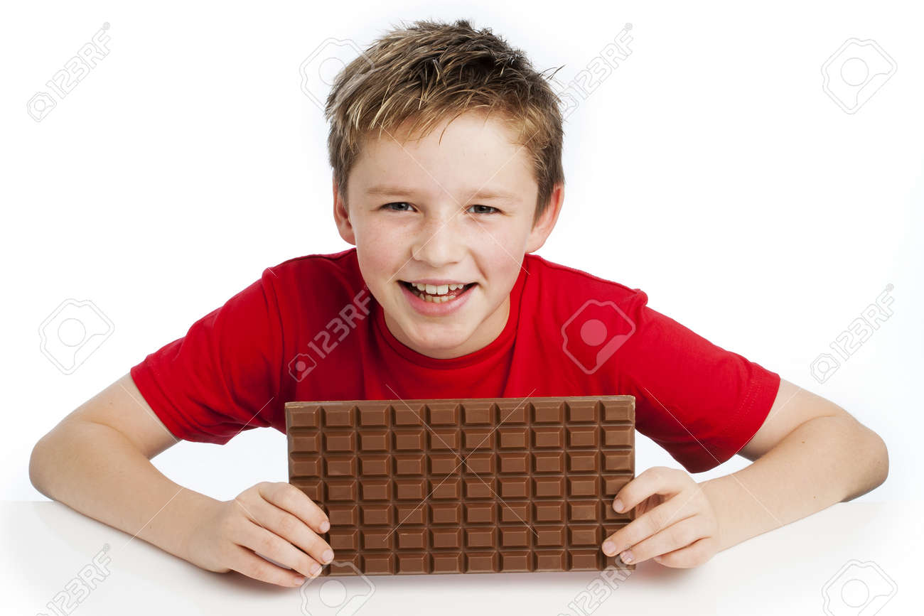 Cute smiling young boy eating a very big bar of chocolate. Wearing a red T-shirt, shot in the studio on a white background. - 20785630