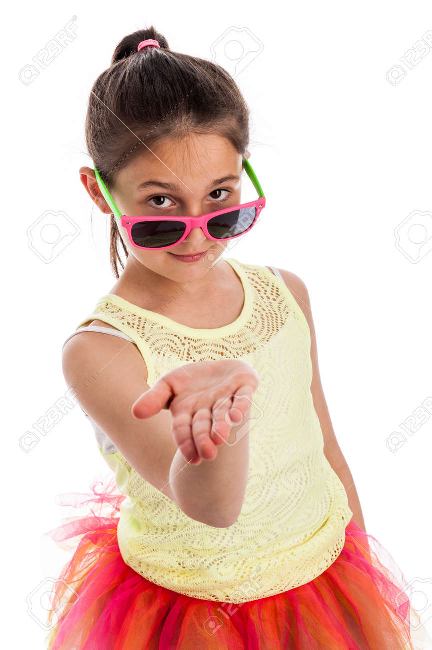 Quirky young girl with colourful cloths, holding her hand out flat, wearing sun glasses and looking to camera. Isolated on studio white background. - 21064105