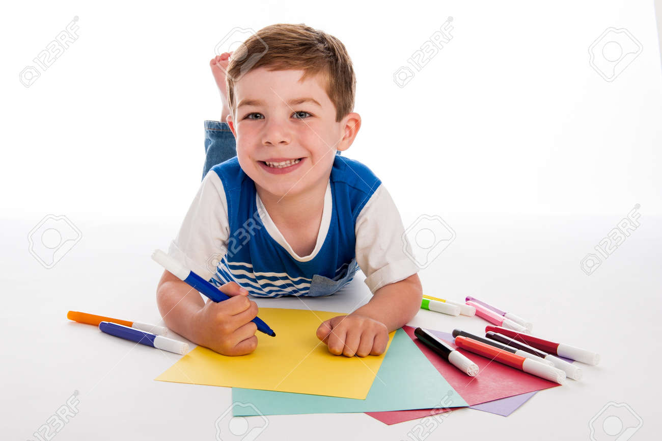 Smiling young boy with felt pens writing and drawing on colourful paper. White background. - 21509662