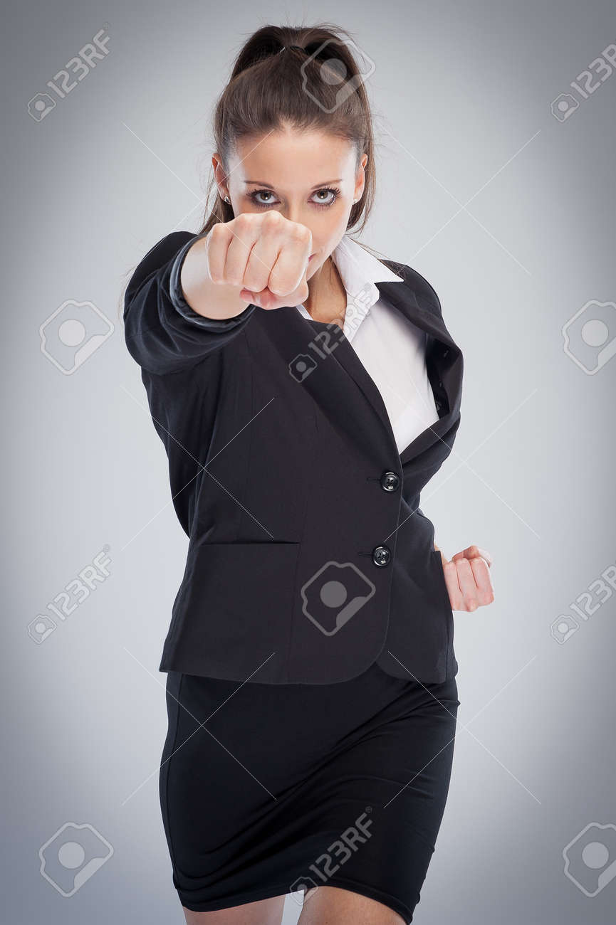 Direct female corporate boss punching at camera. Pose looking straight to camera. - 39787062