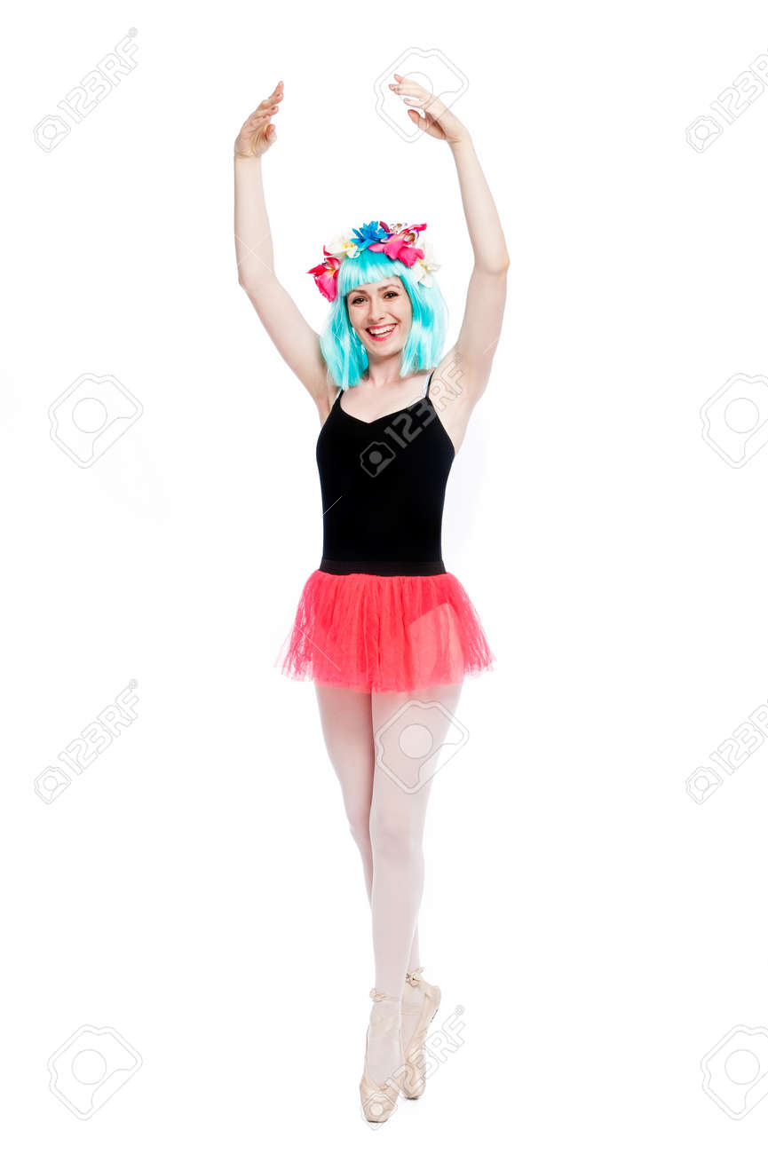Smiling ballet girl in point position with arms up. Shot in studio on white background. - 40550081