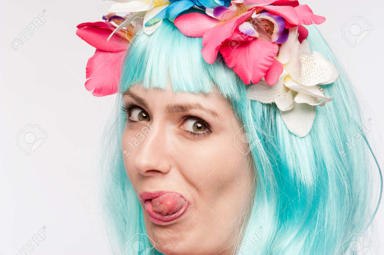 Girl with headdress and blue wig sticking her tongue out in studio on white background. - 42315170